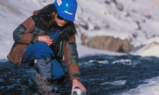 A woman, wearing a hardhat, takes a water sample from a stream.