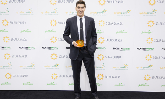 Alexander Palkovsky is holding his award from the Canadian Solar Industries Association.