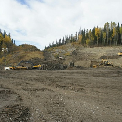 Picture of mining equipment and trucks in an open field.