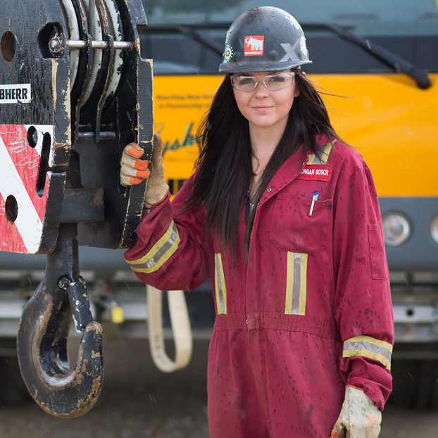 A female student is wearing a hard hat in front of a crane.