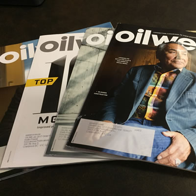 A number of Oilweek magazines spread out on a table.