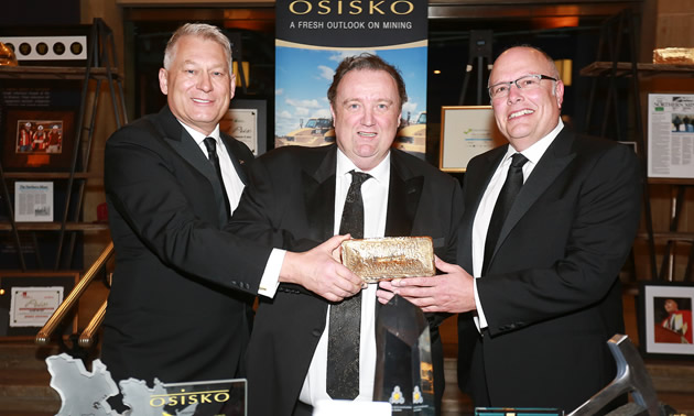 The three co-founders of Osisko Mining are holding Canadian Malartic's first gold bar.