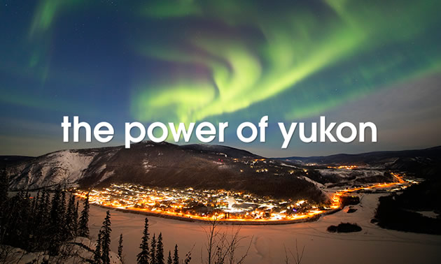 'Power of the Yukon' text, with picture of light-up town at night and aurora borealis in sky.