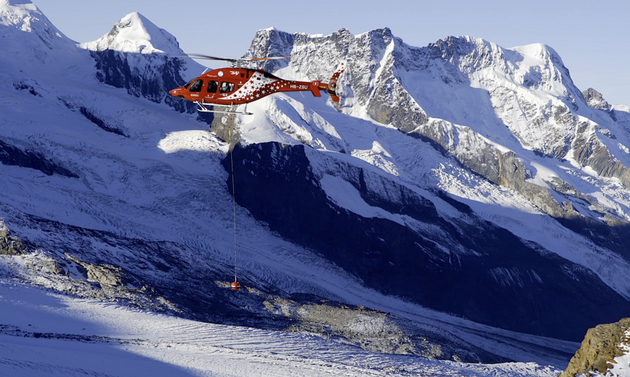 A helicopter is flying low in a snowy mountainous terrain.
