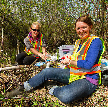 Biologist Elizabeth Vincer on the left with environmental specialist Lori Leach on the right working together in the field.