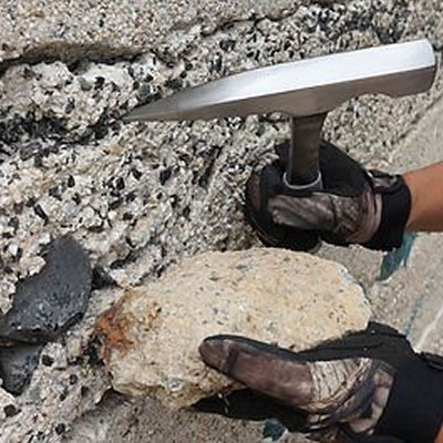Picture of person holding rock hammer.