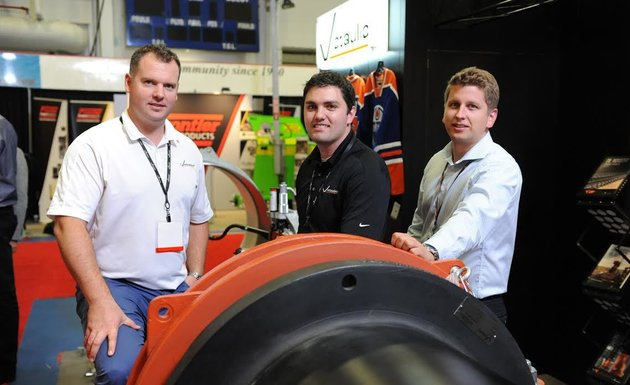 Three participants are at their display at a trade show.