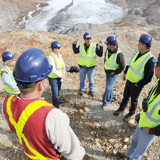 People are gathered in a circle discussing work at a Seabridge Gold mine on the top of a mountain.