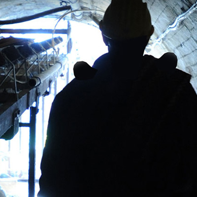 Silhouette of man standing in mine tunnel.