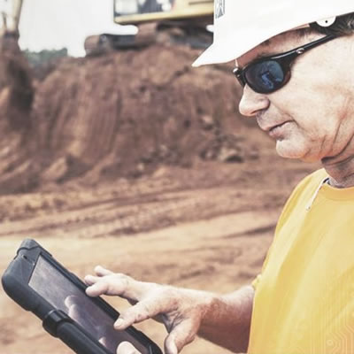 Picture of construction working using iPad on construction site.