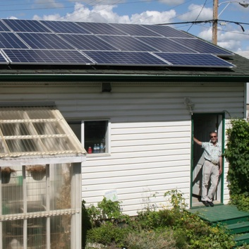 Man standing in the door of his home that has solar panels on the roof.