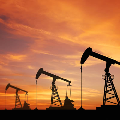 Picture of oil wells, silhouetted against sunset sky, with logo of Stamper Oil and Gas in top corner.