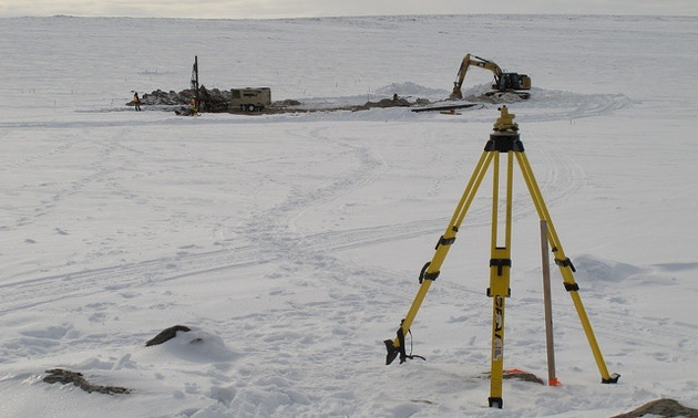 This is the CH-6 trench site on March 20, 2013; the air-track blast-hole drill is on the left, and the excavator is on the right. The tripod is a setup for the surveyor's differential GPS unit used to determine the blast-hole locations.