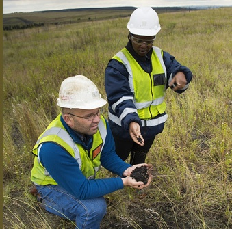 Anglo American Thermal Coal - Environmental - Kleinkopjie Colliery . Gustav Le Roux, rehab planner, and Dolly Mthethwa, environmental co-ordinator, inspect the results of the Fungcoal trials on the Klipan discard dump where a bacteria has been introduced to reduce the rough discard into viable organic material in which plants will grow.