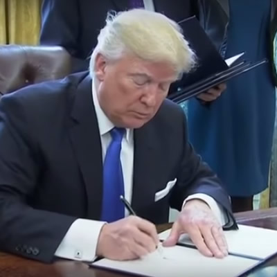 U.S. President Donald Trump signs an executive order, approving the Keystone XL and Dakota Access pipeline projects.