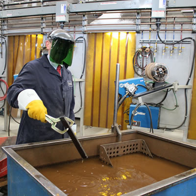 Picture of welding student cooling down steel in a tank.