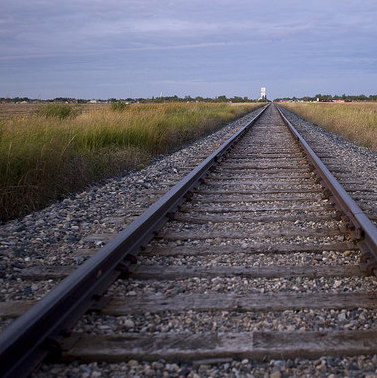 A photo of a railway track running off into the prairies.