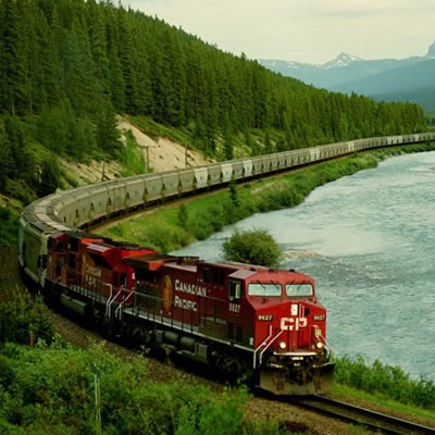 Picture of CP Rail train travelling along bottom of mountain valley beside river.