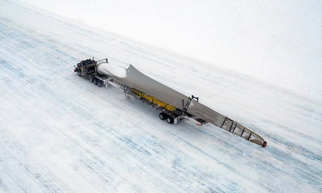 A truck hauling one of the 33-metre-long turbine on an ice covered road.