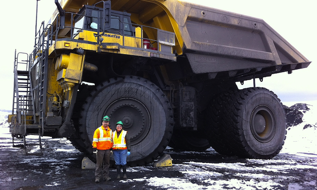 Roland and Elsie Antuna stand in front of a haul truck at Peace River Coal