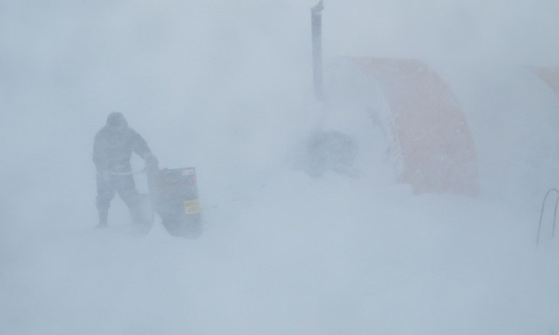 April 4, 2013, was the first day of a four-day whiteout. Here, Daniel Akpalialuk, a worker from Pangnirtung, Nunavut, is shown fuelling one of the tents to keep the camp running.