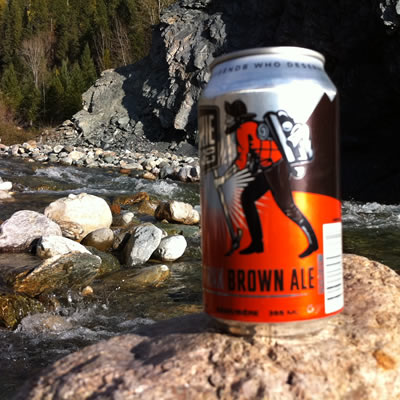 A beer can with a picture of a prospector on it, with a river in the background.