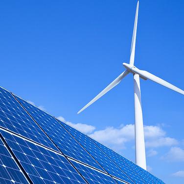 Solar panels and wind turbine against blue sky.