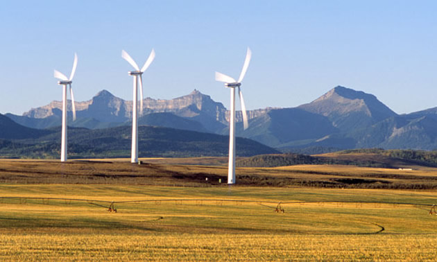 Three wind turbines are located on flat land near an irrigated field with mountains in the background.