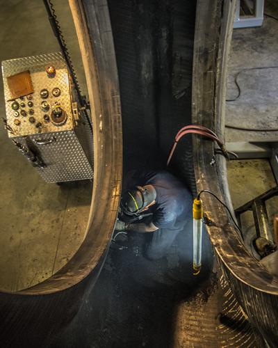 Tire technicians work in dangerous environments when executing a repair inside a truck tire.